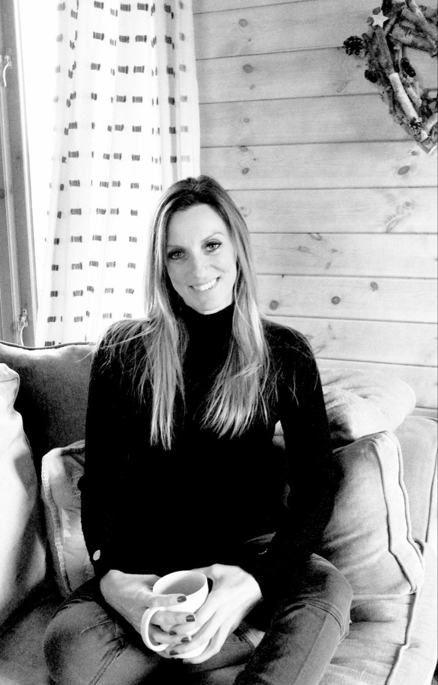 Lisa Edwards sat on a comfy sofa with a mug of coffee looking relaxed and happy in black and white