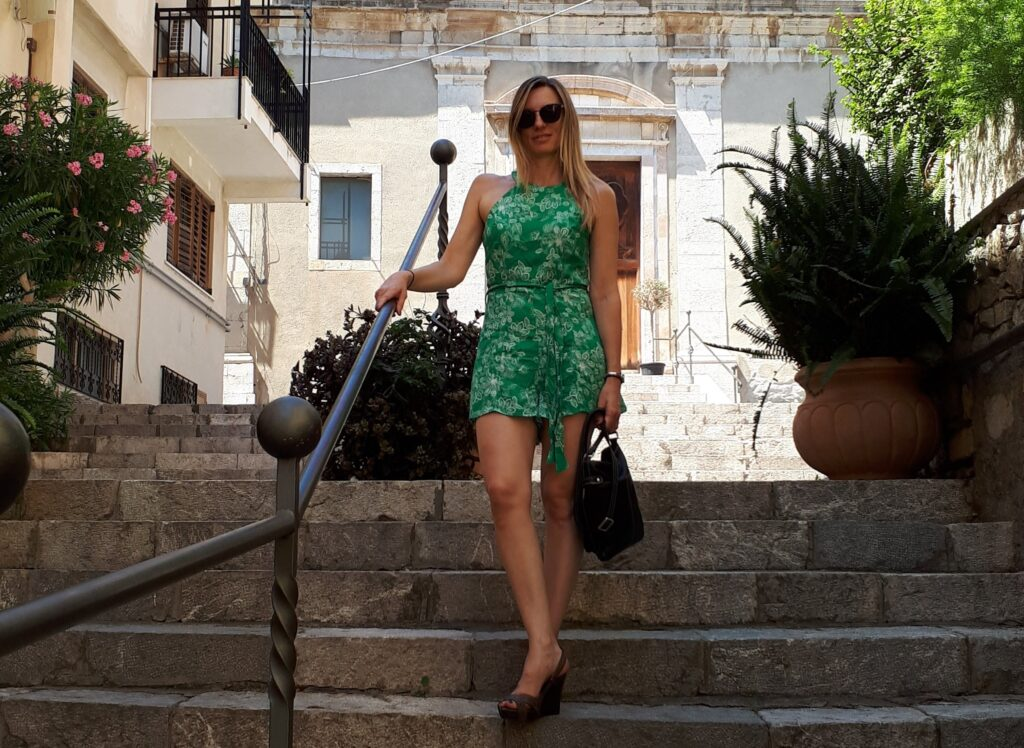 Lisa Edwards standing with self-confidence and self-belief on steps in sicily